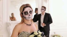 Dziewczyna z okropnym makijażem w postaci czaszki w pokoju z mężczyzną w kostiumu zdjęcie wideo