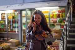 Dziewczyna z pakunkiem mandarynka w wieczór rynku zdjęcie stock