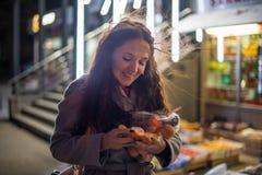 Dziewczyna z pakunkiem mandarynka w wieczór rynku fotografia stock
