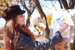 Dziewczyna z paletą w ręce kreśli na papierze Obrazy Stock