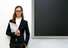 Dziewczyna z papierów kosztami przy blackboard Obrazy Stock