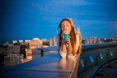 Dziewczyna z papierową filiżanką i drymbą kłama na tle nocy miasto zdjęcie stock