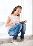 Dziewczyna z pastylka hełmofonami i komputerem osobistym w domu Zdjęcie Royalty Free