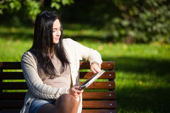 Dziewczyna z pastylki obsiadaniem na parkowej ławce zdjęcia stock