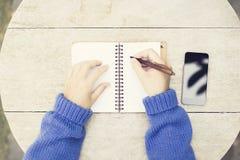 Dziewczyna z piórem, otwartym pustym dzienniczkiem i pustym czarnym smartphone na wo, Obrazy Royalty Free