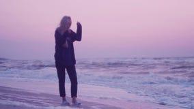 Dziewczyna z pięknym włosy chodzi przy świtem wzdłuż piaska na brzeg, morzem Różowy niebo, fale, wiatr w tle zbiory wideo