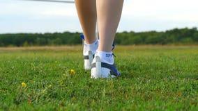 Dziewczyna z pięknymi nikłymi nogami iść na zielenieje pole Zakończenie kobiety ` s cieki w sneakers Sporty i plenerowy zdjęcie wideo