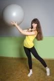 Dziewczyna z piłką robi ćwiczeniom w gym Fotografia Royalty Free