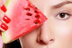 Dziewczyna z plasterkiem arbuz na różowym tle Fotografia Stock