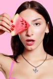 Dziewczyna z plasterkiem arbuz na różowym tle Zdjęcie Stock