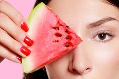Dziewczyna z plasterkiem arbuz na różowym tle Fotografia Royalty Free