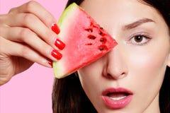 Dziewczyna z plasterkiem arbuz na różowym tle Zdjęcia Royalty Free