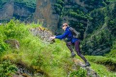 Dziewczyna z plecakiem jest odpoczynkowa w górach Panorama Kaukaz góry zdjęcie stock