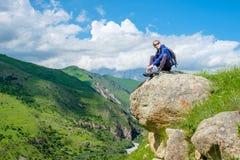 Dziewczyna z plecakiem jest odpoczynkowa w górach Panorama Kaukaz góry obrazy stock