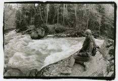 Dziewczyna z plecakiem na ona z powrotem siedzi na brzeg rzeki Zdjęcie Stock