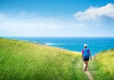 Dziewczyna z plecakiem podróżuje wzdłuż dennego wybrzeża zdjęcie stock