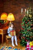 Dziewczyna z prezentem siedzi blisko świątecznej choinki zdjęcia stock