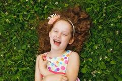 Dziewczyna z princess korony lying on the beach na trawie Obrazy Stock