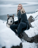 Dziewczyna z psim Malamute wśród skał w zimie Zdjęcie Stock
