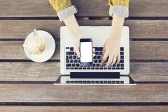 Dziewczyna z pustym smartphone, laptopem i cappuccino na drewnianym tabl, zdjęcia stock
