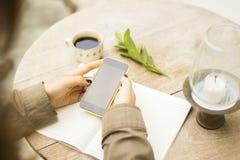 Dziewczyna z pustym telefonem komórkowym, notatnikiem i filiżanką kawy, zdjęcia stock
