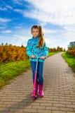 Dziewczyna z różową hulajnoga Fotografia Royalty Free