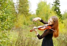 Dziewczyna z skrzypce w lesie Fotografia Stock