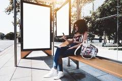 Dziewczyna z smartphone i dwa billboardów szablonami w przystanku autobusowym fotografia royalty free