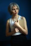 Dziewczyna z srebnym włosy i książką w ona ręki z bliska niebieska tła Zdjęcie Stock