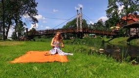 Dziewczyna z suknią siedzi na dywanik stawiającym owocowych szkieł strumienia pobliskim moscie zdjęcie wideo