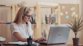 Dziewczyna z szkła Kaukaskim pojawieniem, siedzi przy komputerową słuchawki z mikrofonem daleko i radzi ludzi dalej zdjęcie wideo