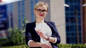 Dziewczyna z szkłami i białym włosy chodzi wzdłuż pogodnej ulicy blisko budynku biurowego Biznesmen ubiera wewnątrz zdjęcie wideo
