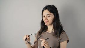Dziewczyna z szkłami odizolowywającymi na popielatym ściennym tle zdjęcie wideo