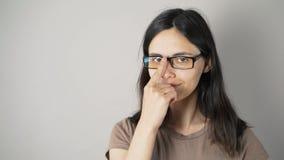 Dziewczyna z szkłami odizolowywającymi na popielatym ściennym tle zbiory wideo