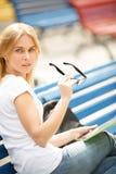Dziewczyna z szkłami w rękach siedzi na ławce Zdjęcia Stock