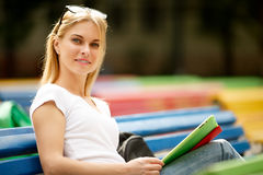 Dziewczyna z tajemniczym uśmiechem i pastylką siedzi na ławce Zdjęcie Stock