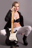 Dziewczyna z tatuażami pozuje z gitarą Zdjęcia Royalty Free