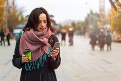 Dziewczyna z telefonem i kawą iść na miasto ulicie zdjęcie royalty free