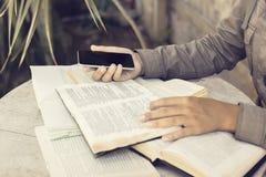 Dziewczyna z telefonem komórkowym i książkami plenerowymi zdjęcia royalty free