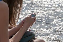 Dziewczyna z telefonem siedzi przy wodą Obraz Stock