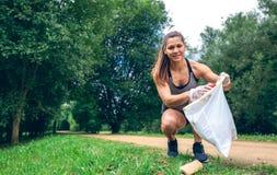 Dziewczyna z torba na śmiecie robi plogging Zdjęcia Royalty Free