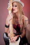 Dziewczyna z udziałami tatuaże pozuje z gitarą Obrazy Stock
