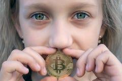 Dziewczyna z w górę zielonych oczu trzyma bitcoin monetę w jej usta Pojęcie inwestuje i handluje łatwy bitcoin zdjęcia stock