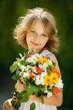 Dziewczyna z wiązką wildflowers outdoors Zdjęcia Royalty Free
