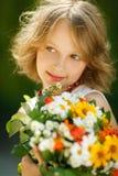 Dziewczyna z wiązką wildflowers outdoors Zdjęcia Stock