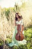 Dziewczyna z wiolonczelą w wysokiej trawie obraz stock