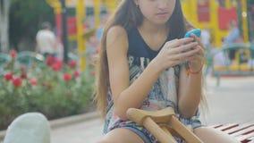 Dziewczyna z złamaną nogą siedzi na ławce na tle opisowy ochraniacz i spojrzenia przy smartphone, zbiory
