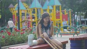 Dziewczyna z złamaną nogą siedzi na ławce na tle opisowy ochraniacz i spojrzenia przy smartphone, zdjęcie wideo