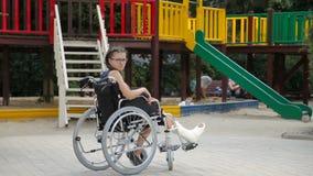 Dziewczyna z złamaną nogą siedzi w wózku inwalidzkim przed boiskiem zbiory wideo