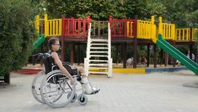 Dziewczyna z złamaną nogą siedzi w wózku inwalidzkim przed boiskiem zdjęcie wideo
